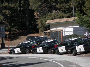 """The Line Up""-Five or six of the California Highway Patrol squad cars were lined up along the embankment on the side of the Hwy. 18 station so the parking lot was free to house a small car show and bounce house for the children."