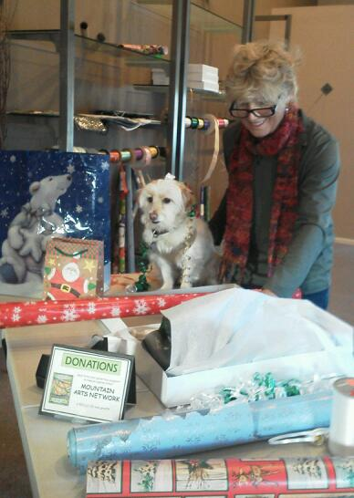 Dayna Perkins is seen wrapping gifts in Lake Arrowhead Village as part of the fundraiser by the Mountain Arts Network. Her adorable dog, Westin, is supervising. The organization is wrapping gifts on weekends to raise money to donate to the Boys and Girls Club.