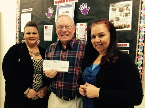 "Lucy ""Luz"" Salinas and Rebecca Prescott, both representing TJ Max presented a $500 check to Dave Stuart of Hearts and Lives."